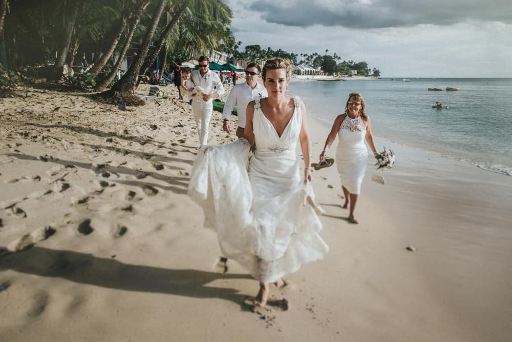 Bride Groom And Members Of The Wedding Party Walking Barefoot Along Beach In Holetown